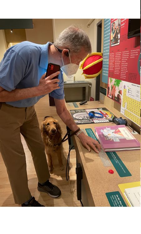 Mike using the Explore app and the Braille labels to experience the museum exhibits